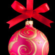 Pink Christmas ball on a ribbon against white background — Stock Photo