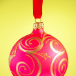 Red Christmas ball against yellow background — Stock Photo