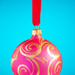 Red Christmas ball against blue background — Stock Photo