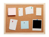 Blank instant photo and note papers on a cork board — Stock Photo