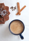 Cup of hot cacao with a chocolate bar, cinnamon and cloves — Stock Photo