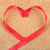Red heart shaped ribbon pinned to cork board — Stock Photo