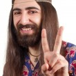 Friendly hippie with long hair making peace sign — Stock Photo