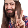 Friendly hippie with long hair making peace sign - Stockfoto