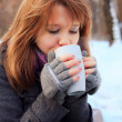 Pretty girl drinking hot tea in winter park — Stock Photo