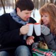 Young beloved couple warming themselves in the winter park - Stock Photo
