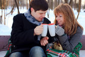 Young beloved couple warming themselves in the winter park — Stock Photo