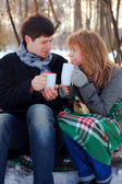 Young beloved couple warming themselves in the winter park — Stockfoto