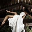 Attractive suntanned girl in white dress poses on a wooden beam. - Стоковая фотография