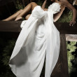 Attractive suntanned girl in white dress poses on a wooden beam. - Lizenzfreies Foto