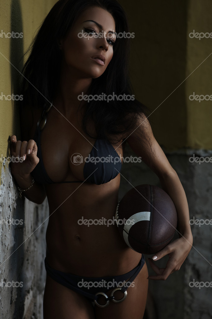Sexual beauty dressed in bikini poses holding a ball for American football. — Stock Photo #4072771