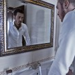 Man takes a look at himself in the mirror. - Stock Photo