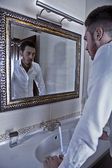 Man takes a look at himself in the mirror. — 图库照片