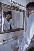 Mann wirft einen blick auf sich selbst im spiegel. — Stockfoto