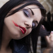 Depressed young brunette with smeared lipstick on her face. — Stock Photo #4775187