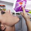Beautiful brunette on background of an open refrigerator - Stock Photo