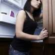 Beautiful brunette on background of an open refrigerator — Stock Photo