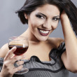 Stock Photo: Studio portrait of beautiful brunette holding a glass wine.
