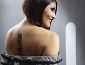 Portrait of a pretty girl with tattoo on her back — Stock Photo