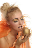 Beautiful woman in gold with apple — Stock Photo