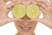 Young woman holds halves of lime before eyes — Stock Photo