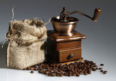 Coffee mill with a sack of roasted beans — Stock Photo