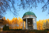 Pavilion in a park with yellow birch trees and blue sky on backg — Stock Photo