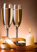 Two glasses with champagne and candle — Stock Photo
