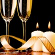 Foto Stock: Two glasses with champagne and candles