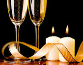 Two glasses with champagne and candles — Stock Photo
