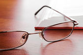 Glasses close-up and open book — Stock Photo