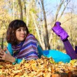 Young girl lying in autumn fall leaves — Stockfoto #4066412