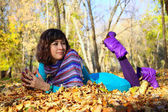 Young girl lying in the autumn fall leaves — Stock Photo