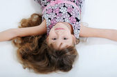 A beautiful little girl lying on the floor — Stock Photo