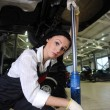 Woman lift car in repair center - Stock Photo