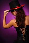 Beauty woman in black corset and silk hat — Stock Photo