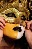 Woman in golden half mask — Stock Photo