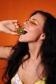 Beauty young woman eat kiwi — Stock Photo