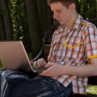 Stock Photo: Young man using laptop in summer park