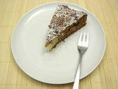 One slice of pear cake on a white plate dusted with powder sugar — Stock Photo