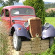 Rusted veteran car jacked up in the open countryside - Foto de Stock