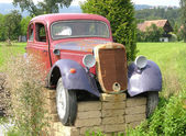 Rusted veteran car jacked up in the open countryside — Stock Photo