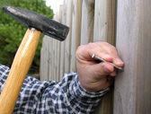Man bangs a nail into a wooden wall — Stock Photo
