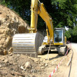 Stock Photo: Yellow digger working on a site