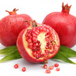 Pomegranate fruits with green leaf and cuts isolated — Stock Photo