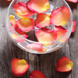 Glass bowl with water and flower petals — Stock Photo #4220834
