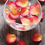 skleněná mísa s vodou a květinové lístky — Stock fotografie
