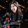 Stock Photo: Brunettte guitar player girl in the night