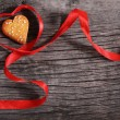 Foto Stock: One cookies and heart shaped red ribbon