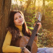 Beautiful brunette guitar player girl — Stock Photo